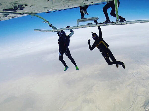 Hanging underneath a helicopter before a skydive